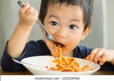 2 years old mixed race Asian boy eating pasta.Boy look hungry and pasta sauce messes all around his face while having breakfast.His dish almost empty.Concept of healthy and  enjoy eating child.