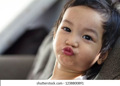 2 years old mixed race Asian baby boy with his lips puckered up blowing a kiss,baby giving a kiss,xoxo. Concept of happy healthy child.