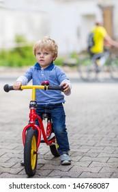 2 years old toddler boy having fun on bicycle in summer