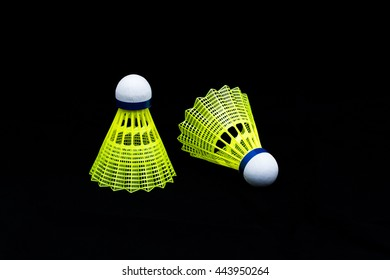 2 Yellow Plastic Badminton shuttlecock in black background with reflect and spacing for text - sport equipment isolated on black.