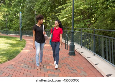 2 young african american college students walking along a sidewalk on campus