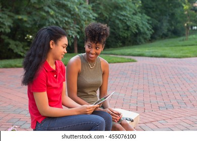2 young african american college students looking at a tablet together