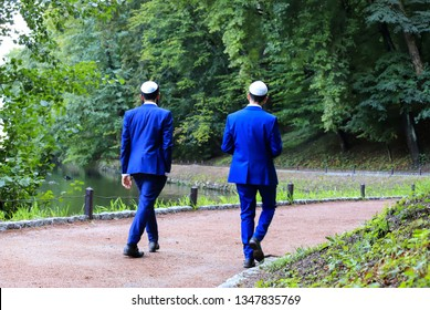 2 Young men, Hasidic Jews in blue suits and white cap walk in the park in Uman. Ukraine,  Jewish New Year.