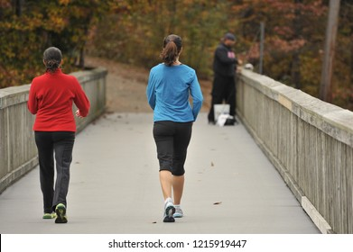 2 young women walk briskly over a bridge in the Fall