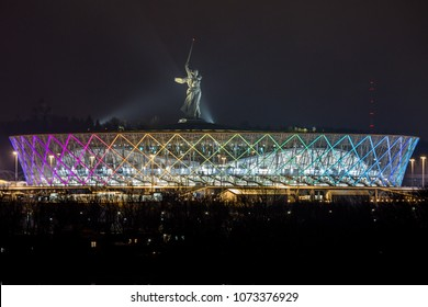 20 April, 2018 Volgograd, Russia. Famous statue The Motherland calls on the top of the new football stadium Volgograd Arena, illuminated in the night. View from the other side of the Volga river.