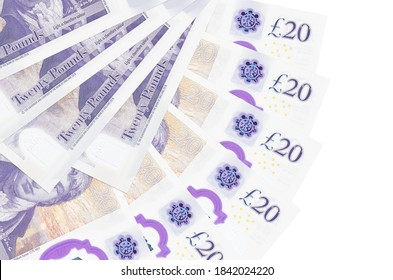 20 British pounds bills lies isolated on white background with copy space stacked in fan shape close up