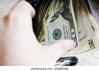 20 twenty dollar bills inside wallet. American currency in paper form.