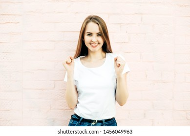 20 year old girl in white T-shirt rejoices over pink wall background. Female with blue eyes and perfect white teeth.