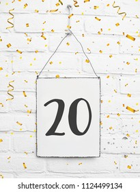 20 years old birthday party card text with golden confetti, number twenty, metal plate white brick background