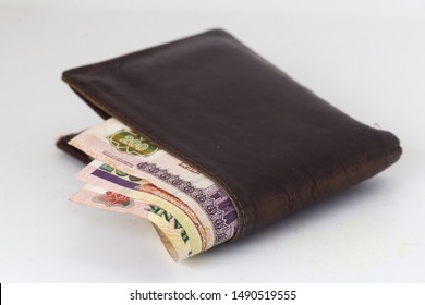 200 Egyptian pound bills in a dark brown wallet isolated on a white background