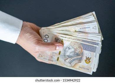 200 Polish zlotys. The man is holding his hand one hundred banknotes. Polish currency.