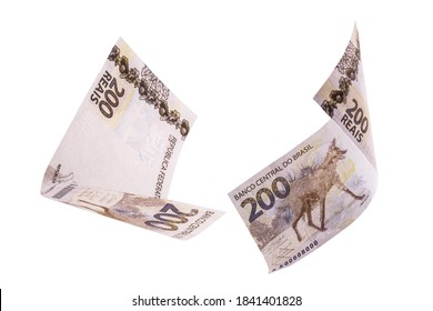 200 reais banknotes, bank notes falling on isolated white background. Two hundred reais from brazil, selective focus. Fall, inflation and loss concept