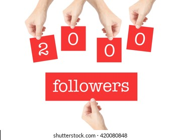2000 followers written on cards held by hands