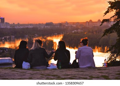 20.04.2018. four young girls on Kalemegdan fortress park hill looking warm colorful sunset on Danube river  with horizon of New Belgrade in background in Belgrade, Serbia