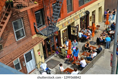 20.05.2016. Outdoor table and chairs of restuarnt bar with people on the streets in downtown manhattan under high line in new york