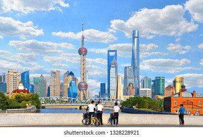 20.05.2017. local people with bicycles observe historical Waibaidu bridge in front of the futuristic modern skyline of Pudong Shanghai, China