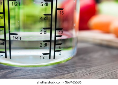 200ml / 2dl Of Water In A Measuring Cup On A Kitchen Counter With Vegetables