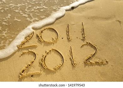 """""""2011 2012"""" written on sand."""