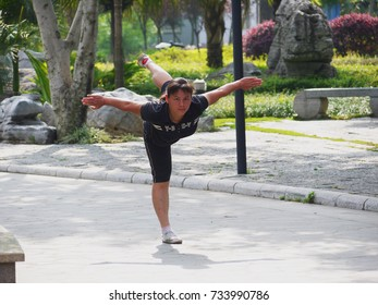 2011.5.24, in Liuzhou, China. a middle-age female citizen practicing Chinese Kong Fu in a local park. Kong Fu can be used as a form of exercise to keep human body fit and flexible.
