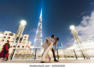 2013 DECEMBER 20 - DUBAI, illustrative editorial.  Beautiful couple in wedding dresses on honeymoon, posing for pictures in Dubai. DESTINATION WEDDING, TRAVEL, LUXURY, NEW TRENDS CONCEPT
