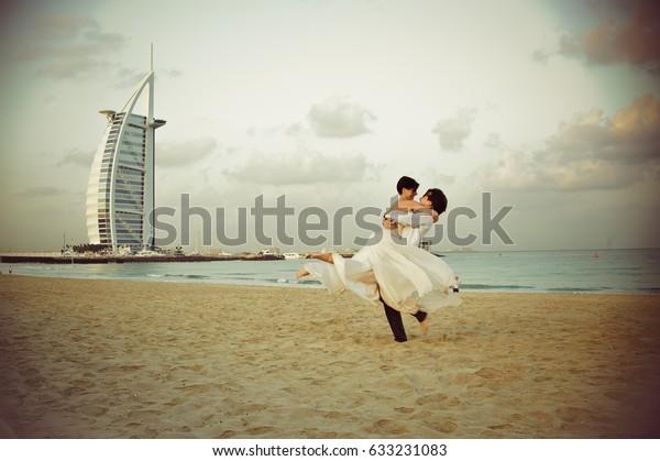2013 DECEMBER 20 - DUBAI, illustrative editorial.  Beautiful and cheerful couple in love on honeymoon, celebrating in a beach of Dubai. DESTINATION WEDDING, TRAVEL, LUXURY, NEW TRENDS CONCEPT