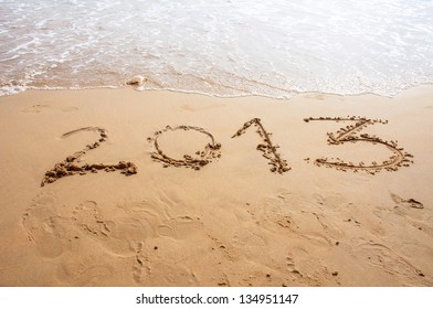2013 written in the sand on the beach in summer