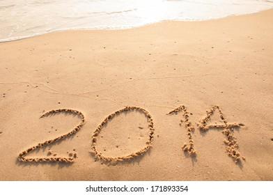 2014 written in sand on the beach