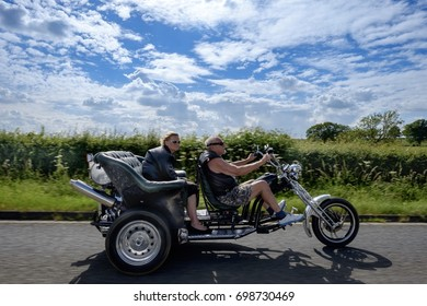 2015, Oxford UK - An elderly couple riding in style with their classic look custom black and chrome coloured motorcycle on a bright summer day