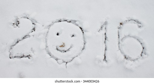 """2016"" written on snow surface, background close up."