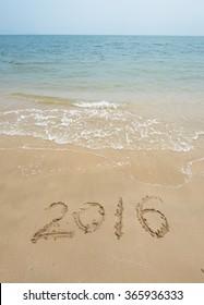 2016 written in sand, on tropical beach
