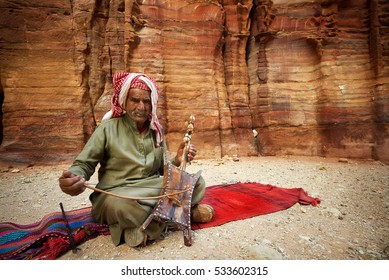 2016-04-27 An old man playing traditional Bedouin Rababa string musical instruments near tomb 67. Ancient city of Petra, Jordan