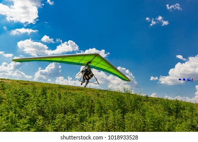 2016-05-09, Kyiv, Ukraine. Pilot runs with a hang glider on a green grassy slope with blue sky and clouds above