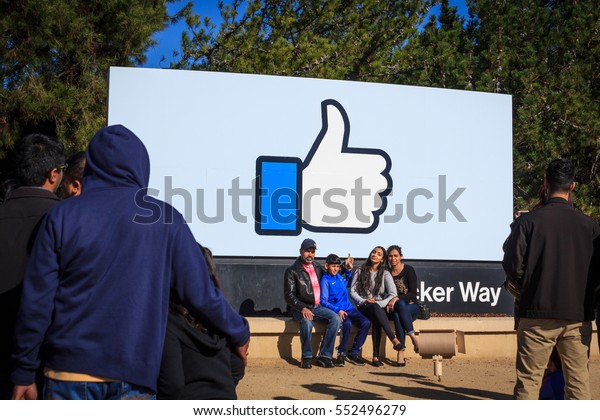 "[2016-12-26] Facebook Headquarters, 1 Hacker Way, Menlo Park, California, USA. Facebook ""like"" sign at the entrance sign board and visitors taking photo against it are on this photo"