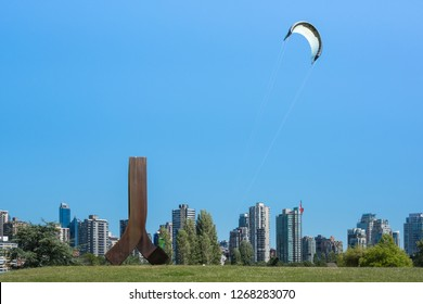 2016-June-26: Gate to the Northwest Passage sculpture made out of corten steel located at Vanier Park. A person kite rollerskating on a sunny day.