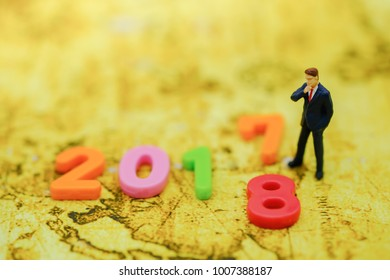 2017 and 2018 New year Concept. Closeup of businessman minature figure standing with colorful plastic number on map.