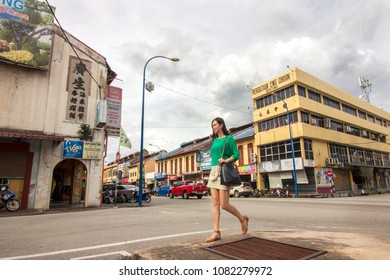 2017 Dec 05 Pahang, Malaysia - an attractive asian lady tourist walking on the street of Bentong with the old historical shop lots in background. the town is famous for Musang King Durian