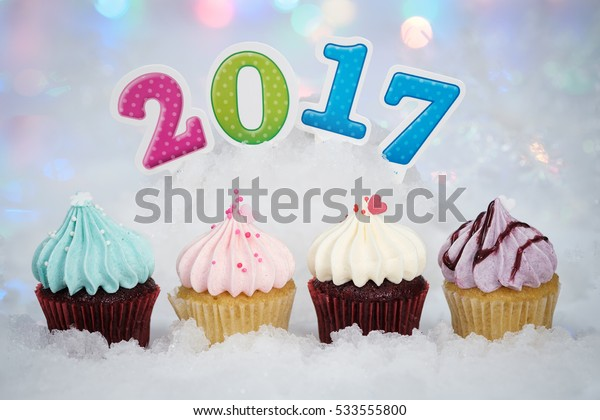 2017 Happy New Year Cupcakes on ice with bokeh background.