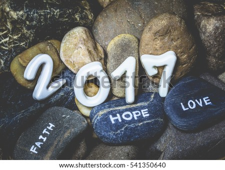 2017 happy new year with word faith hope love on the river stone