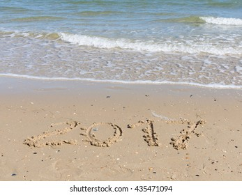 2017 inscription on a light yellow sand fines with small stones and fragments of shells on the sandy beach and small wave of clean sea water with white foam