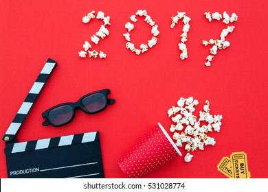 2017 made of pop corns. clapper board,  movie tickets, 3d glasses in red background.Flat lay