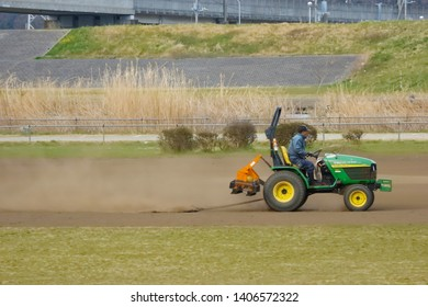 2017 March 19. Tokyo Japan. A worker man cleaning soil ground by tracktor car to preapre for agriculture.