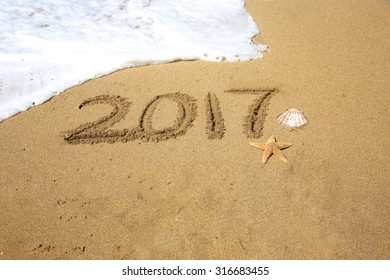 2017, a message written in the sand at the beach.