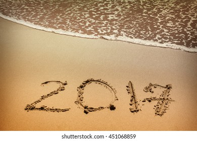 2017, message written in the sand at the beach background