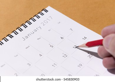 The 2017 new year calendar  on the brown paper background with the red pencil on the hand