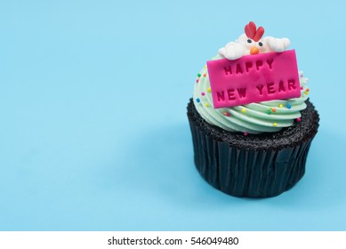 2017 new year chicken cupcake over blue background with copy space