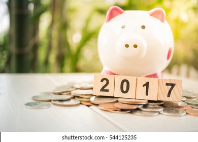 2017 New year wooden blocks and  piggy bank on piles of money. Cash savings growth concept.