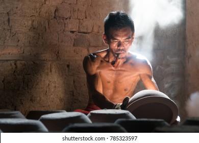 2017 October 1 Ratchaburi, Thailand. Middle-aged man potter checking pot in pottery workshop.