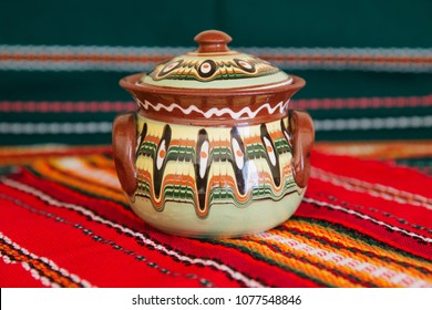 2017 October - Bulgaria, Balchik - traditional Bulgarian ceramic pot made in Troyan technique  on traditional table clothes of green and red color.