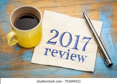 2017 review text on a napkin with coffee against grunge wood desk