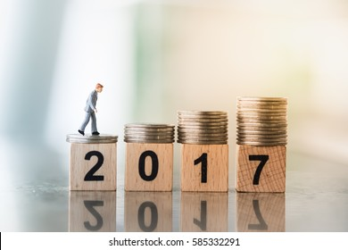 2017 Year and business finance concept. Businessman miniature figure walking top of stack of coins with 2 0 1 7 number wooden block toy.